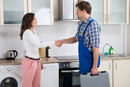 43306223-young-male-repairman-shaking-hands-with-happy-woman-in-kitchen